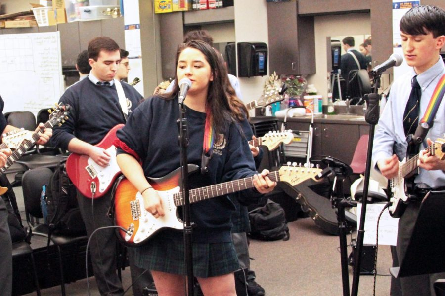 Senior Caroline Hall and her Advanced Guitar classmates practice their set for the Fine Arts Assembly