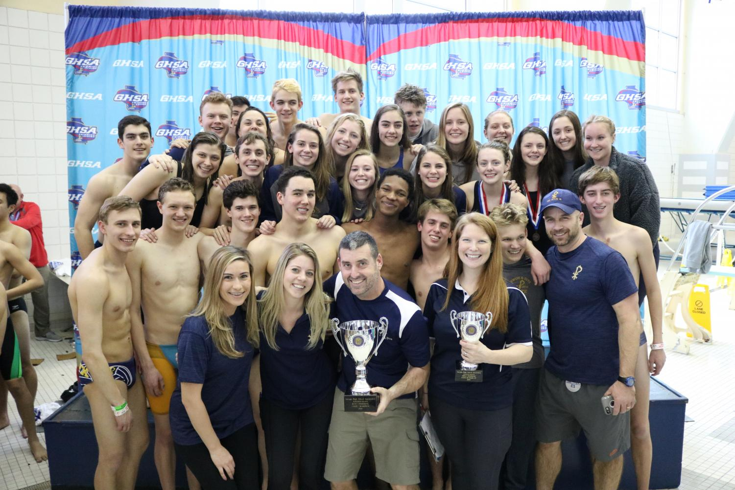 The boys' and girls' teams show off their 1st and 2nd place trophies at the state meet on Saturday, February 9.