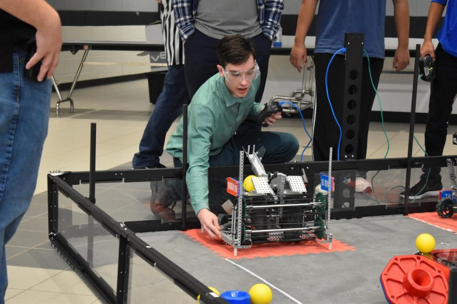 At a VEX Robotics competition this winter, senior Powell Whitaker works with a robot that he and his partner, senior Mitchell Philipp, built earlier in the year.
