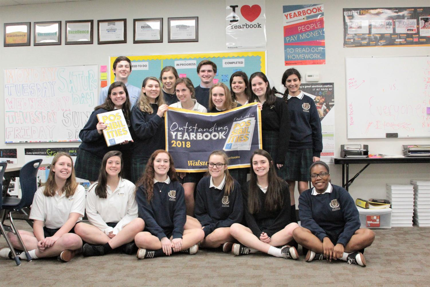 "The yearbook staff shows off the banner they received after being included in ""Possibilities,"" an annual book from their publishing company that recognizes ""yearbooks with the highest levels of design, photography, and coverage."""