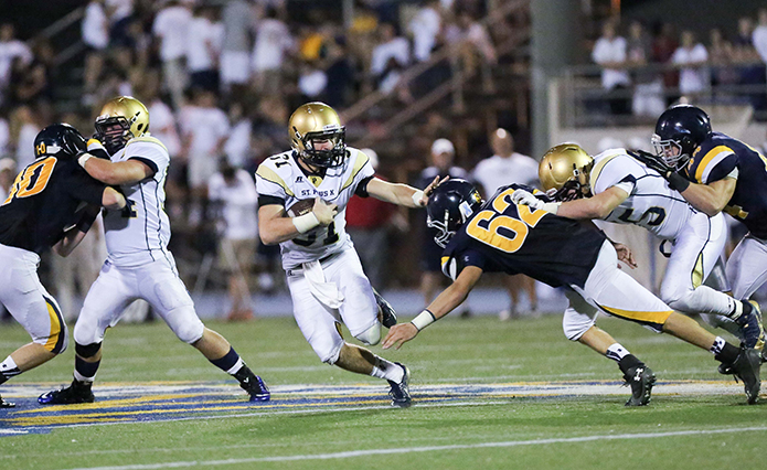 St. Pius running back Ransom Klinger (#31) stiff arms a Marist player as he runs through a hole created by the Pius offensive line.