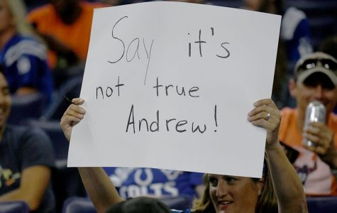 A Colts fan hold up a sign expressing her sadness  after learning that star quarterback Andrew Luck was suddenly retiring.