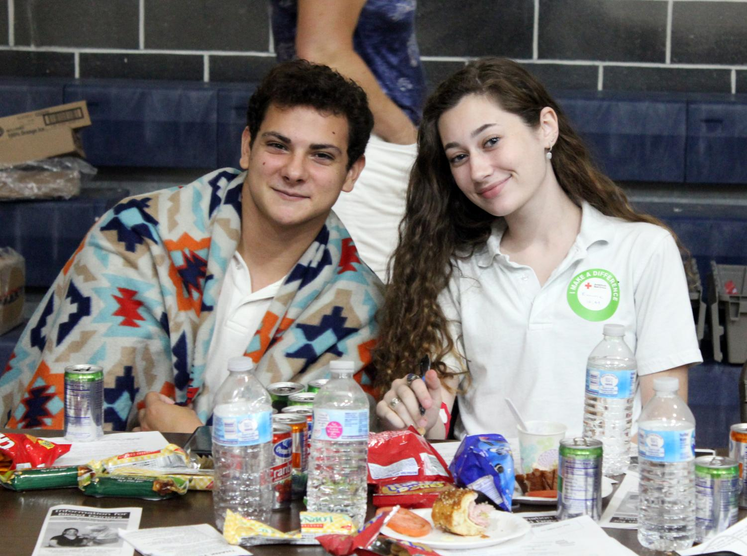 Seniors Nick Nowack and Emma Foy sit at the snack table after donating blood last spring. Their contributions helped St. Pius X earn the