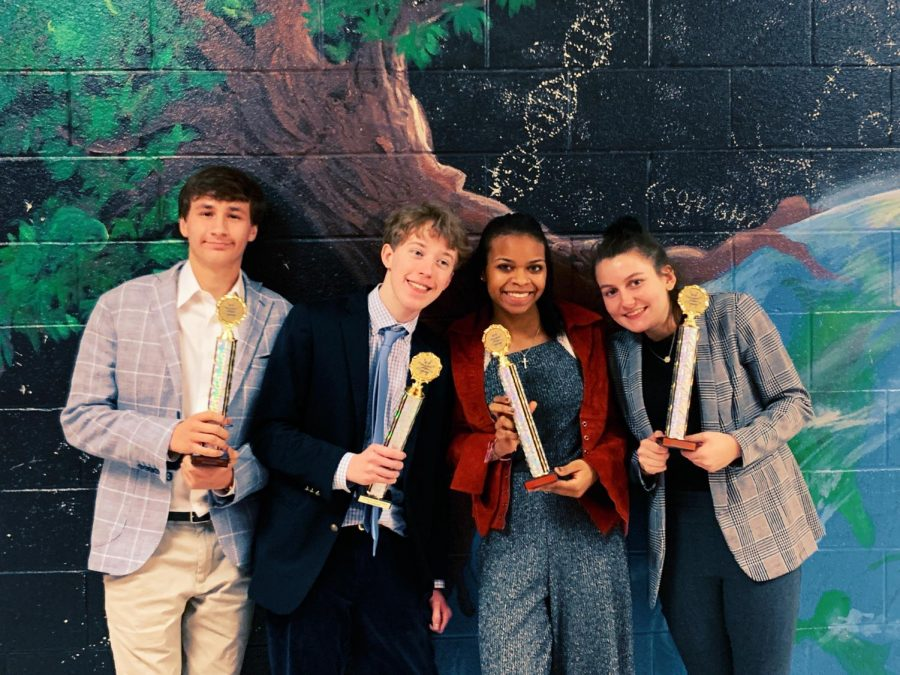 Seniors Austin Lalomia and Witt Hollensbe show off their finalist trophies with two competitors from Walton High School at a competition last year.