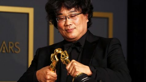 """Parasite"" director Bong Joon-ho celebrates with two of the four Oscar statues his film won at this year"