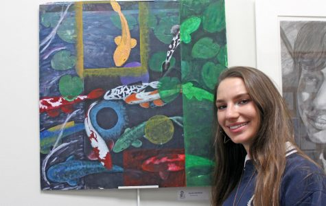 Senior Lauren Ratchford stands next to a painting titled