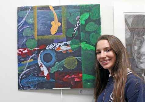 "Senior Lauren Ratchford stands next to a painting titled ""Community"" that she submitted to Juried Arts Exhibition."
