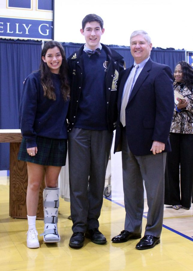 Valedictorian Nicole Gresham and salutatorian Daniel Buckely smile with Mr. Spellman upon hearing their names announced after an all-school mass in January.