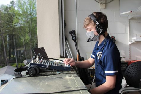 Sophomore Tripp Buhler sets up his equipment in the press box before a varsity lacrosse game in March. Buhler and his ESPX crew also broadcast football, basketball, and soccer games.