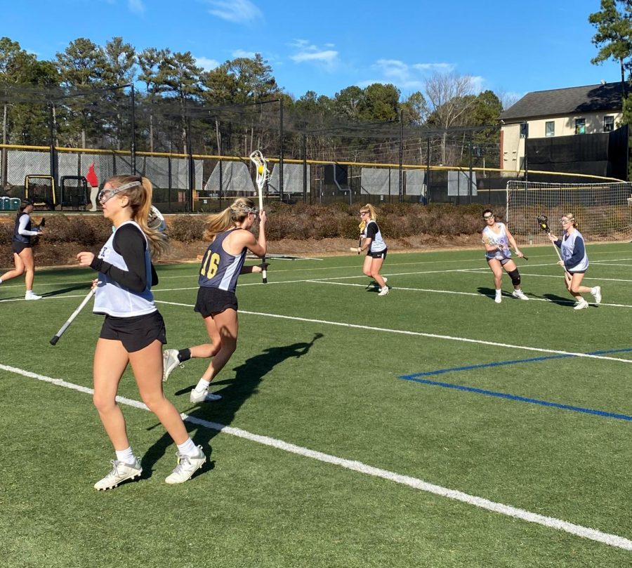 The varsity girls lacrosse team practices one day after school in February. Their conditioning throughout the fall and winter helped prepare them for the long season ahead of them.