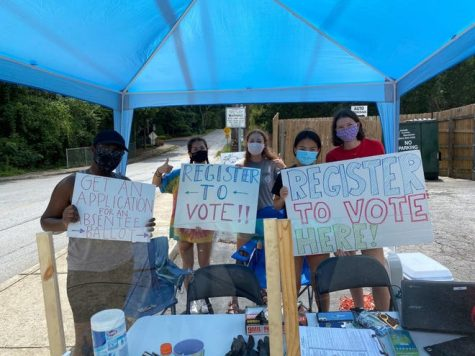 Junior Ava Nieman (2nd from right)  stands at a booth outside Oak Grove Market last fall to encourage young adults to register to vote.